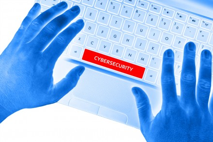 """Hands on laptop with """"CYBERSECURITY"""" word on spacebar button."""